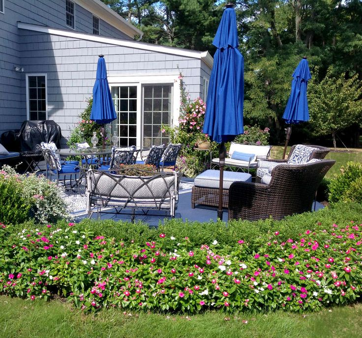 Three equally vibrant umbrellas are staggered around the patio for aesthetic balance and functional shaded cover from the sun. #interiordesign #outdoorpatiodesign #patiodesign #terracedesign #paintedconcrete #monmouthcounty #virginiatesidesigninc #blue umbrellas #outdoorfurniture #blueoutdoorfurniture #cobaltblueumbrellas #sunbrella