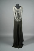 """Barbra Streisand Custom Vintage Dress - black polyester evening gown, label reading, """"An original design Registered by a member of Fashion Originators Guild,"""" featuring attached heavily beaded cape, 1-inch straps, mini covered button closure at back."""