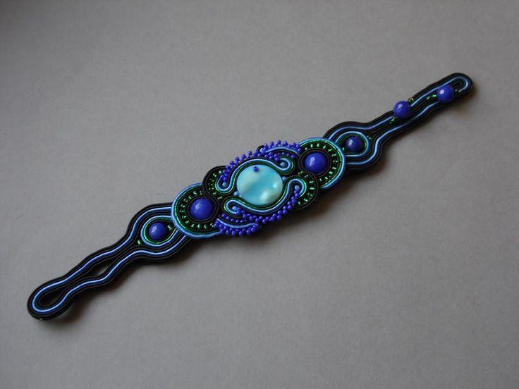 Bransoletka wykonana w technice haftu sutaszowego. Część kompletu.W centrum masa perłowa i jadeity obszyte koralikami szklanymi.Wykończone filcem.