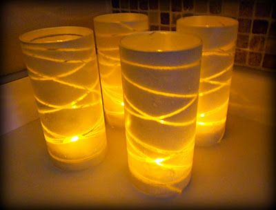 Dollar Store Glass Vase Luminaries- just need spray paint, yarn, tape, and glass vases. Only cost about $1 to make each one.