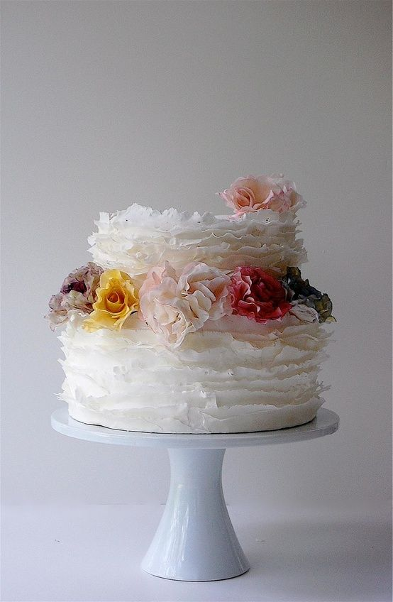 Two tier white frill wedding cake with colored sugarpaste ...