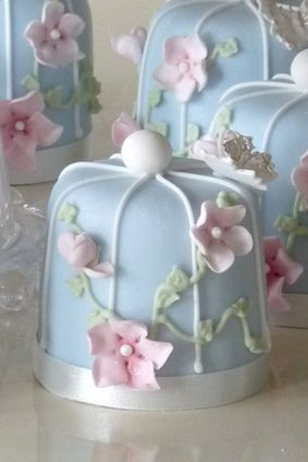 Light blue petits fours with white piping, pink flowers, and ribbon