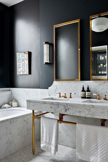 An extremely chic bathroom by Hackett Holland.  Black walls with marble and gold hardware