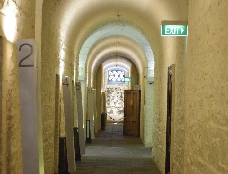 An underground corridor with doorways on either side.