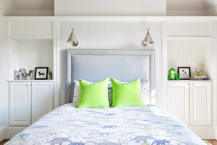 This neutral kid's room proves that a space doesn't have to be colorful to be fun and playful. Built-in cabinets flank both sides of the bed, creating functional and stylish bedside tables. An upholstered headboard with two rows of nailhead trim is custom-built to fit the space, and reading lights above are a practical addition. Dinosaur-printed bedding and a pair of acid green pillows bring punch and kid-friendly flair.