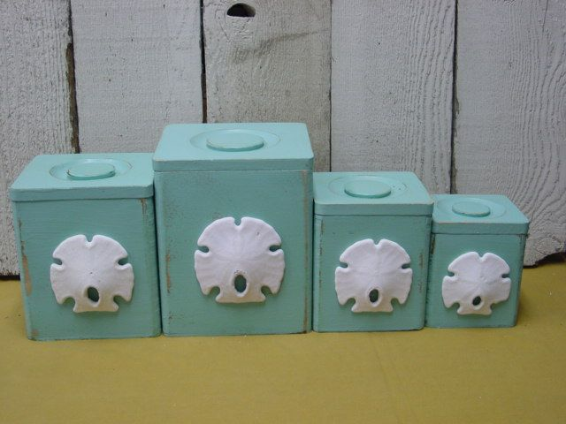 WOODEN CANNISTERS PAINTED DISTRESSED WITH SAND DOLLARS GLUED ON. IDEA FOR LAURA, PAINT THEM METAL FOR THE INDUSTRY PART OF IT AND ADD SAND DOLLARS