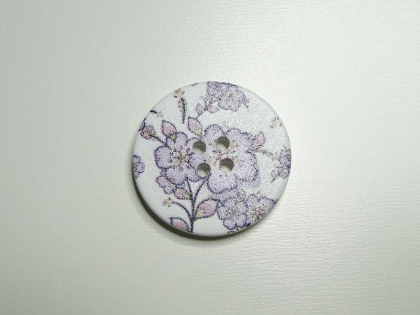 Witte houten knoop met lila bloemen