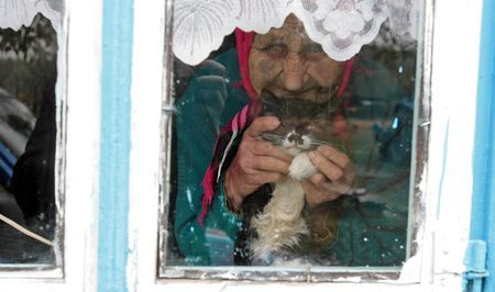 Old woman and cat Photo by Vladimir Cheberkus — National Geographic Your Shot