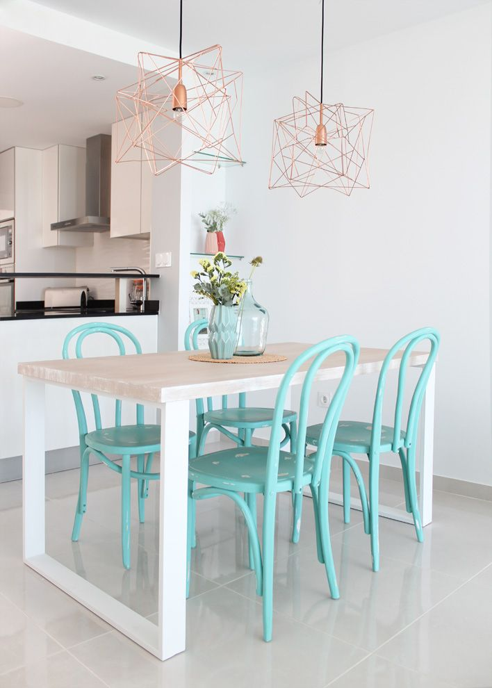 Modern open concept kitchen and dining room. Copper geometric pendant light, turquoise bentwood chairs, white walls, bleached wood and white modern dining table, pale grey tile floors.