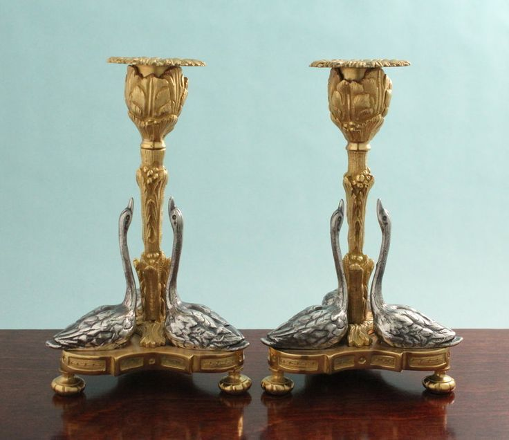 """Pair of gilded bronze candlesticks with three facing silvered swans mounted upon the tri-form base. Central detailed foliate-and-berry columns lead to foliate candlecups with their complementing, detachable bobeches. The candlesticks float upon notched bun feet. France circa 1890. 7 1/8"""" H., 4 1/4"""" W.  Offered by Cherub Antiques Gallery: http://www.cherubantiquesgallery.com/"""
