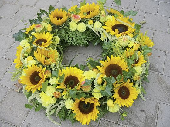 Sonnenblumen im Kranz! Unsere prämierten Meisterfloristen fertigen Ihren individuellen Blumenkranz an.