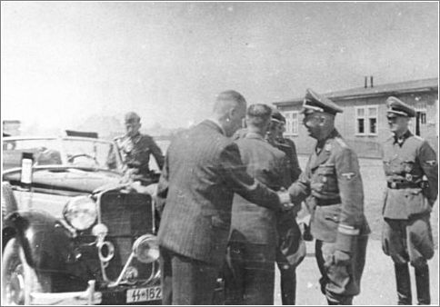 Reichsfuehrer SS Heinrich Himmler shakes hands [probably with an IG Farben representative] during a tour of the Monowitz-Buna building site.