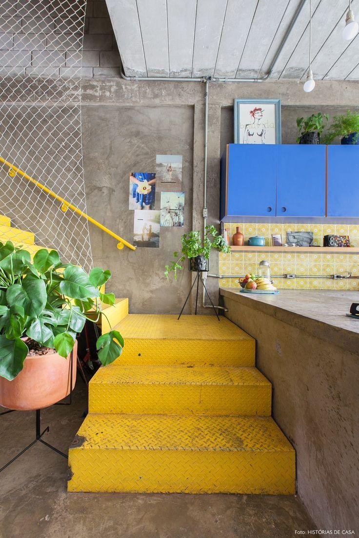 Cozinha colorida com paredes e piso de cimento queimado, armários na cor azul, azulejos estampados e escada metálica amarela.