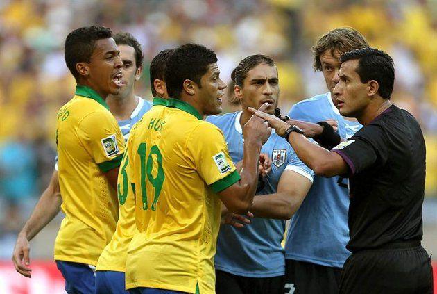 GRA416. BELO HORIZONTE (BRASIL), 26/06/2013.- Jugadores de las selecciones de Brasil y Uruguay discuten una jugada con el árbitro Enrique Osses (d) tras sacar tarjeta a marilla al defensa brasileño Da