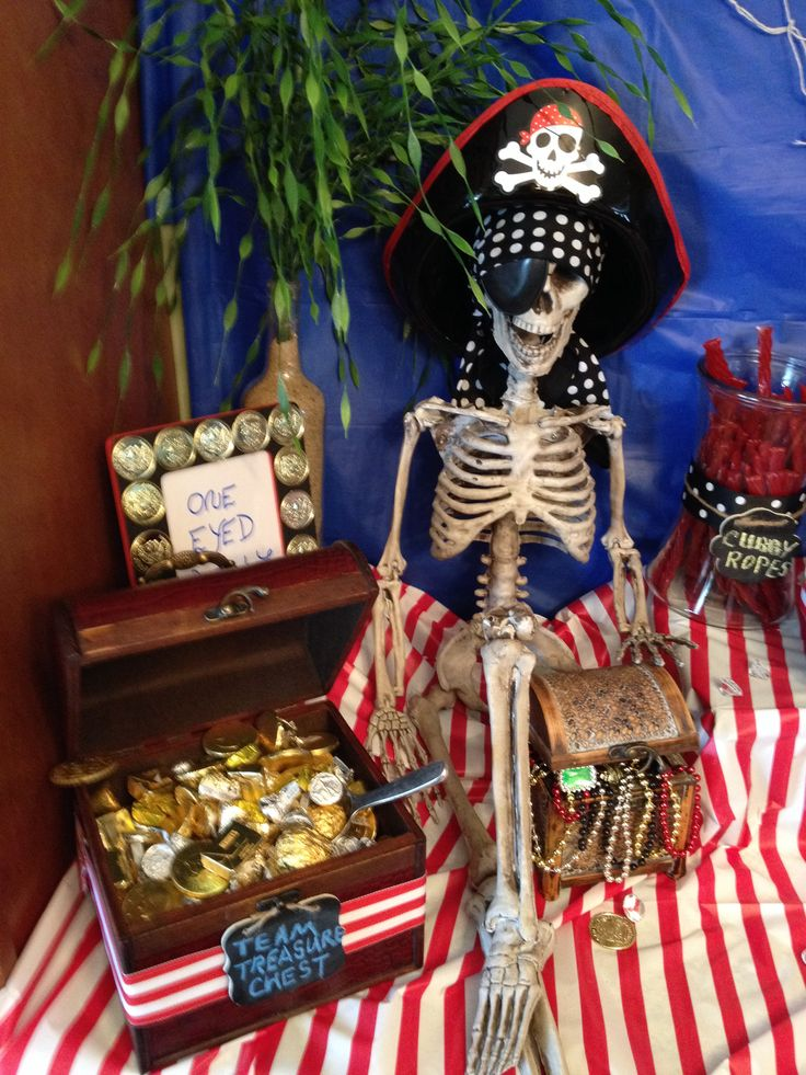 Pirate display. Filled wine bottle with sand and plastic seaweed plant. Painted $1 wooden frame & added plastic gold coins. Jakes Team Treasure Chest-ferrero rocher balls, chocolate coins, dove caramel, Hershey nut bars, chocolate kisses and rolos chocolate. Used this skeleton from Halloween decor. Put bandana, hat, eye patch on him and called him One-Eyed-Willy from The Goonies Movie with his own treasure box.