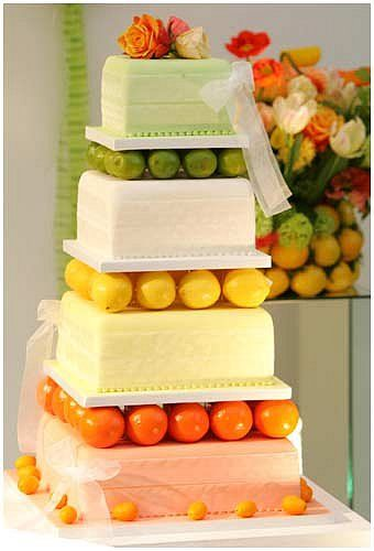 Fresh, fun, whimsical, creative and stylish citrus themed wedding cake featuring unique real fruit tiers in a palette of orange, lemon, and lime.