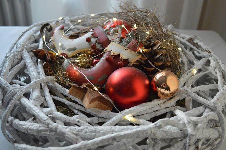 Mit weißer Farbe besprühter Kranz mit Moos, Kugeln, Lichterkette und kleinen Schlittschuhen dekoriert