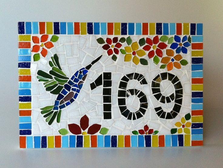 Placa com número residencial para áreas externas feita em base cimentícia. Trabalho em mosaico com pastilhas de vidro e cristal. Acompanha argamassa para ser assentada em muros, paredes ou pode ser feita com furos para ser afixada com parafusos. <br>Pode ser feita também em outros tamanhos e motivos. Consulte-me que terei o maior prazer em lhe responder! <br> <br>Tamanho: 20 cm de largura x 30 cm de comprimento.