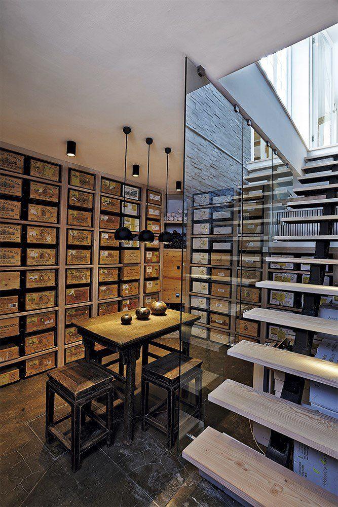 Vinkælder // De dekorative vinkasser står på et skinnesystem, så de er lette at rulle ind og ud. Selve hylderne er lavet af Dinesen-træ, ligesom trappen. Bord og skamler er fra Rosmosegaard Antik. Pendlerne er købt hos Luceplan, som den øvrige belysning i huset