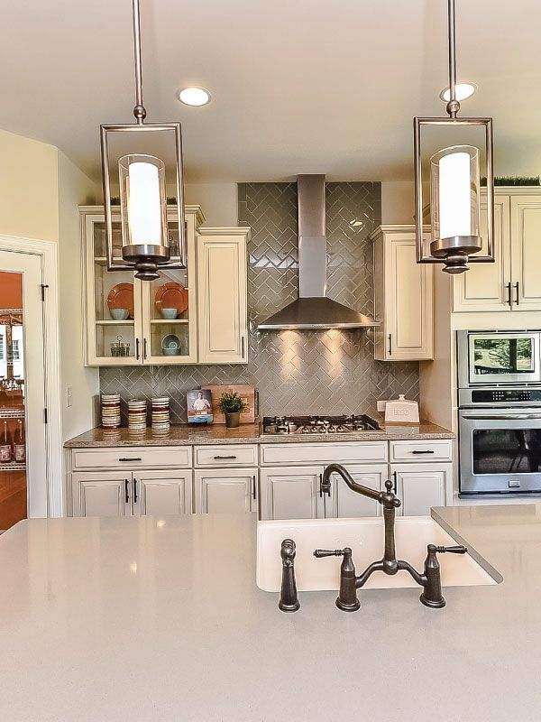 Grey Quartz Countertops, A White Farm Sink, Pendant Lighting, And White  Cabinets Complete