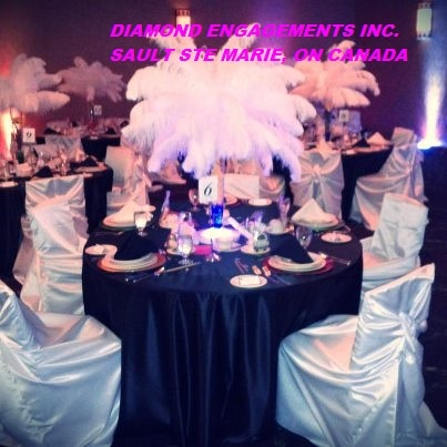 Centerpiece with flowers topped with ostrich feathers and multicolor uplighting