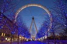 The London Eye is a giant Ferris wheel situated on the banks of the River Thames in London, England. It is the tallest Ferris wheel in Europe, and the most popular paid tourist attraction in the United Kingdom, visited by over 3.5 million people annually; Wikipedia
