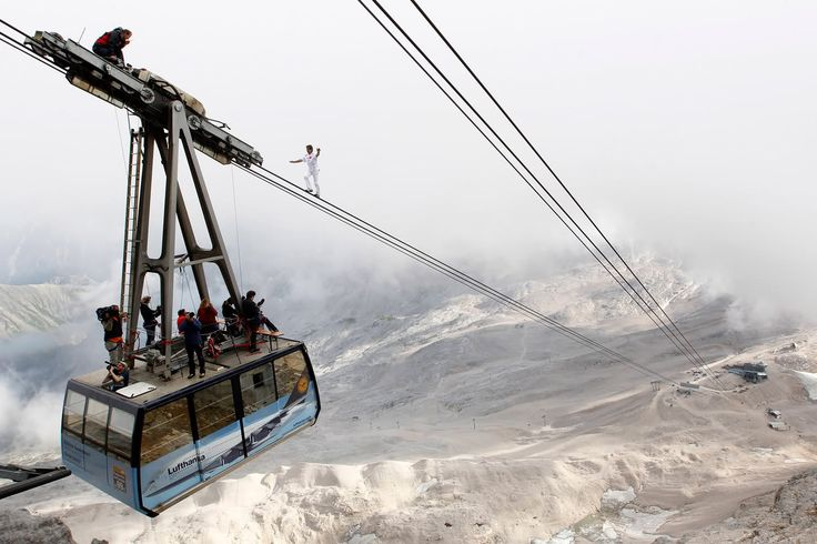 THE DEFINITION OF EXTREME: Freddy Nock from Switzerland balances on the ropeway of a cable car leading to Germany's highest mountain, the 9,718-ft. (2,962 m) Zugspitze, near the southern Bavarian resort of Garmisch-Partenkirchen