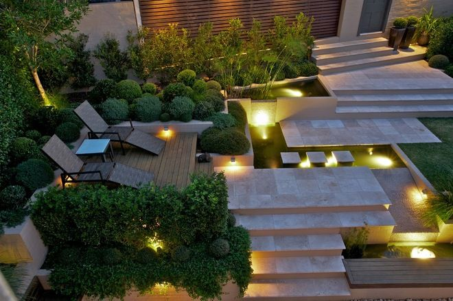 Garden Levels Transform a Steep Slope with several tumbled travertine patios, each connected with elegant stone stairs and contemporary landscape by Art in Green