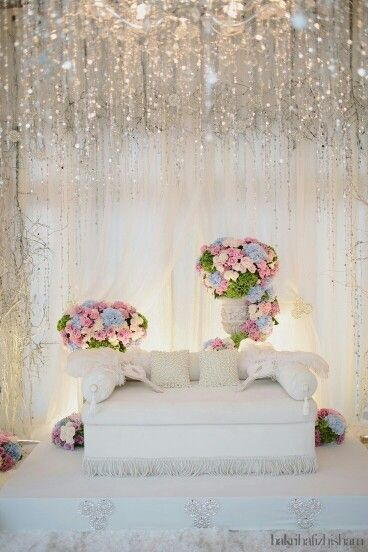 Wedding stage- white, glitzy, pink and blue floral arrangements
