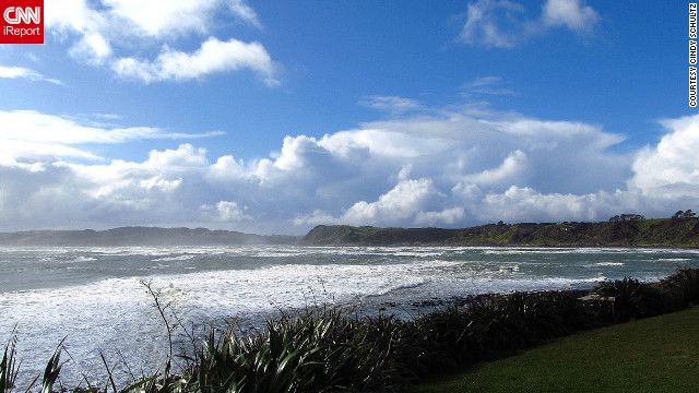 """After Cindy Schultz captured this image of clear skies and calm water at Raglan Beach, New Zealand, the weather dramatically changed before her eyes. """"Blue skies and white puffy clouds gave way to dark skies and black clouds within a matter of minutes,"""" she says. """"It was beautiful, whether the water was blue or gray."""""""
