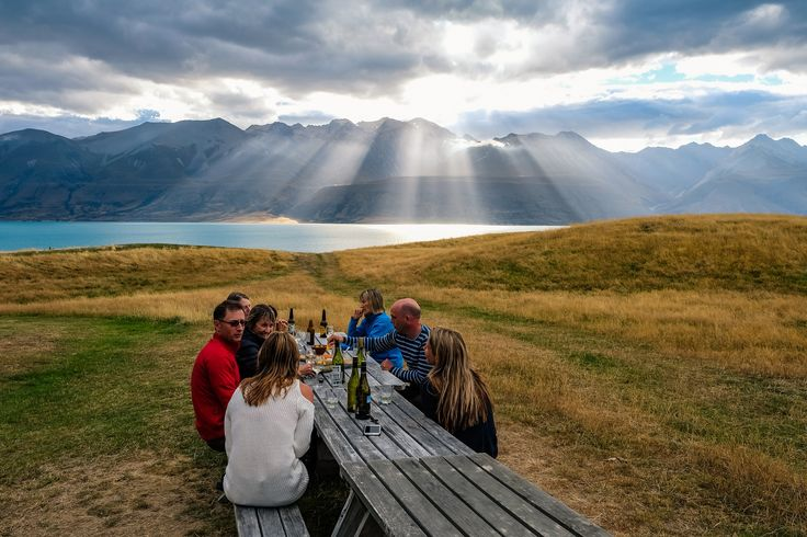 Brian Holsclaw's photo of a group dining outside at Braemar Station, with Lake Pukaki glowing in some incredible light. Brian travelled on a Rimu in February.#newzealand#southisland #hiking#adventuretravel#photography