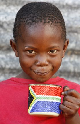 A boy drinking out of a beaded mug with the South African flag on it.