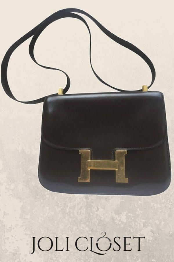 54429f35c2f849 A timeless classic, the Hermès Constance is an epitome of class and  elegance. The bag in dark brown is a crossbody bag with a brass clasp.