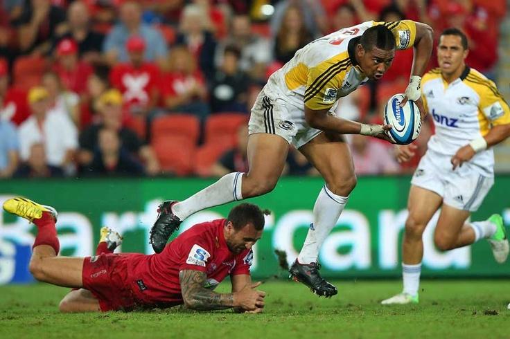 Julian Savea runs through the Reds' Quade Cooper