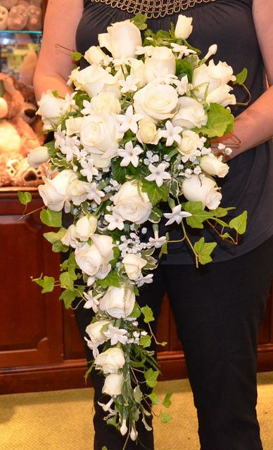Laura Cascade Bouquet of white roses both tea and sweetheart sized, stephanotis, babies breath and ivy. If you like it, repin it because perhaps cascades bouquets will make a comeback!