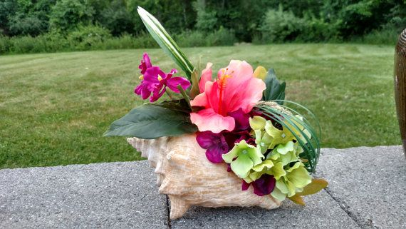 This beach themed centerpiece is made of a conch shell filled with tropical flowers. It is 6 inches tall and 10 inches wide. The perfect centerpiece for you summer luau and is ready to ship today.