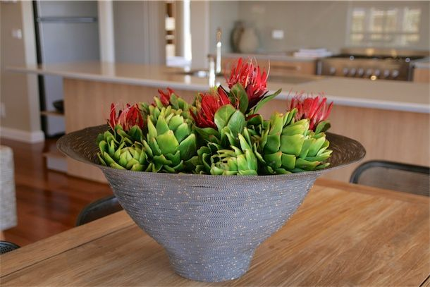 Decorative elements for dining.  Basket with artificial artichoked and native flowers.