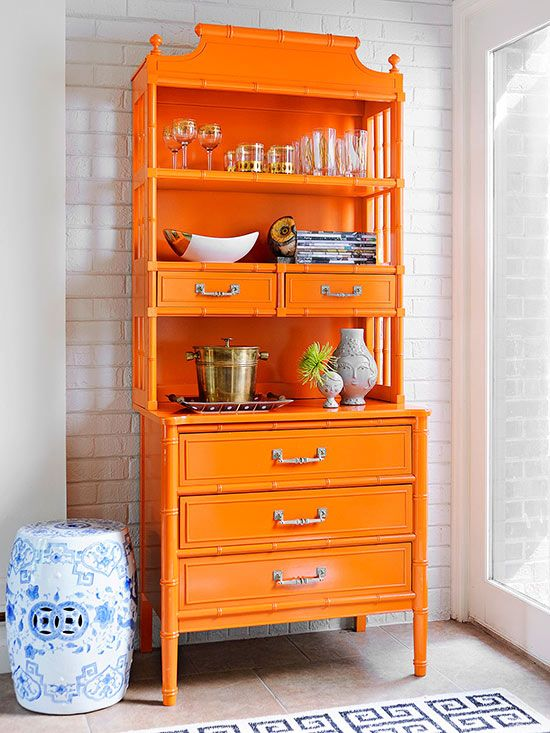 Better Homes & Gardens A vintage pagoda/faux bamboo shelving unit has been painted orange and is used here in a dining room for storage. It combines beautifully with a blue and white Chinese garden st