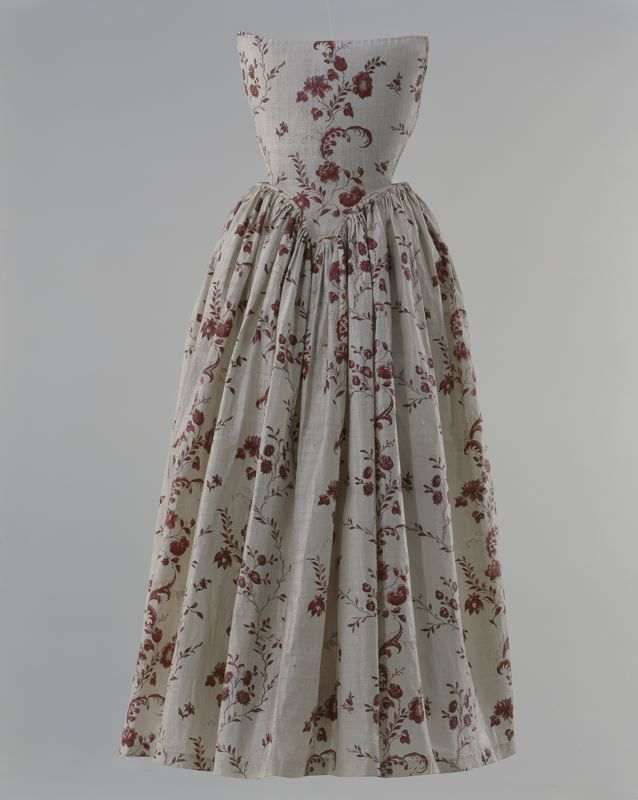 Apron with bib, 1740-1760. Block printed cotton with a pattern of meandering flower branches in red.