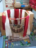 Adding additional props such as hula hoops and fabrics allows children to build more complex construction when playing with wooden blocks.