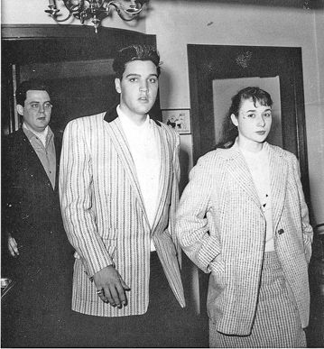 Lamar Fike, Elvis and Hannelore Knab are pictured at the Hotel Bayerischer Hof in Munich, Germany on June 15, 1959. Hannelore Knab worked as freelancer for the Bayerischer Rundfunk ( = Bavarian Broadcasting, BR), a public-service radio and television broadcaster, based in Munich. On that day she managed to win Elvis for an exclusive interview in his hotel room. With her little nose and her freckles she looked like his 12-year-old cousin, Elvis told her.