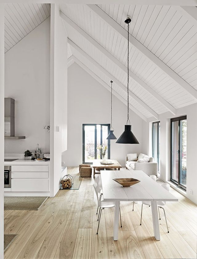 Modern white kitchen inspiration in an open vaulted ceiling great room featuring pale pinewood floors, a white table and chairs, and black industrial pendant lights - Neutral Home Decor & Decorating Ideas - sarahshermansamuel.com