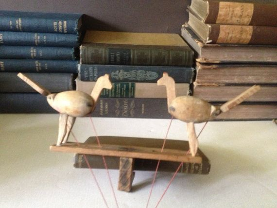 Antique Folk Art Wooden Chicken Toy KH  Handmade antique folk art wooden chicken toy. Attaches to a table top with ball and strings to move the tails and heads to show the chickens eating. Very sweet & unique showing a wonderful timeworn patina from age & play. There is a wood peg at the back to tighten the screw to hold to a table surface...I have it on a small book in the photo.  Measures; 11 from tail ends  In fragile condition, the strings are well worn from their many years, but ...
