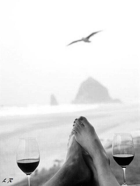 The sea, toes touching and a glass of wine.