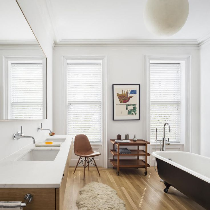 A bathroom in Brent Allen Buck's Brooklyn brownstone with midcentury furnishings and sleek fixtures to compliment the more traditional clawfoot tub.