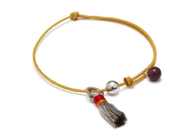 Verstelbare armband op okergeel touw met zilverkraal, paarse porseleinkraal en pompon van Louise Kragh - www.legoutdescouleurs.be