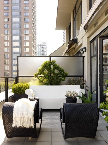Black & White Condo Balcony ~ A builder-basic condo divider calls for some greenery. ~ A trellis acts as a focal point above this Philippe Starck Bubble Club Sofa the same way a mirror or piece of art would above an indoor sofa. Modern patio furniture stands out against the Vancouver skyline.