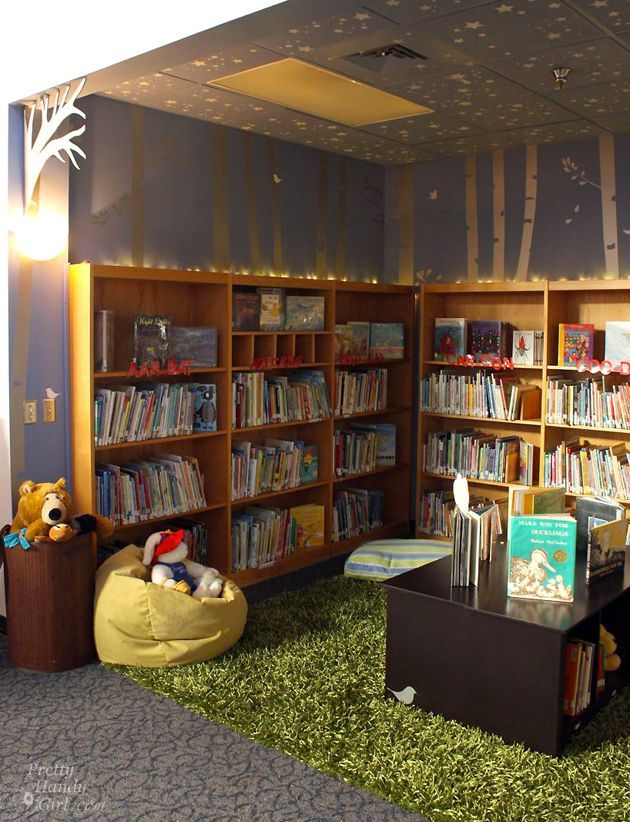 School Library Reveal | Pretty Handy Girl - Mrs. J's Notes: I ADORE the string lights above the bookcases and the wall sconce light instead of the flourescents. Also, the green carpet looks like grass and makes the space so natural looking. Ceiling tiles are painted too with silvers stars!