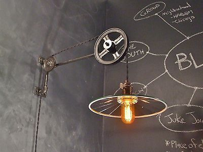 the industrial pulley lamp. Ours is modeled on the same classic designs of the Machine Age and built by hand with industrial grade components. The sleek minimalist fixture features a steel body with cast iron and brass fittings, two chic metal pulley wheels, and a reproduction antique light socket with an aged brass finish and classic flat paddle switch. Wired up with 9 loving feet of new vintage style twisted cloth cord and industrial wall plug.