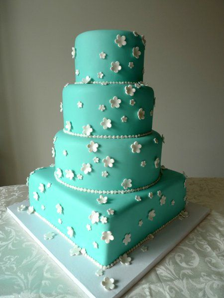 "Tiffany blue cake adorned with white blossoms. The cake sizing is Round 6"",8""…"